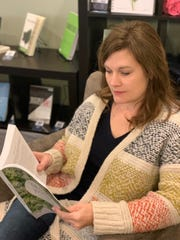 """Jennifer Morgan, pictured here in January 2020, thumbs through the book she wrote with 13 other adoptive moms: """"Grace for the Journey: A One-Year Devotional for Adoptive Moms."""""""