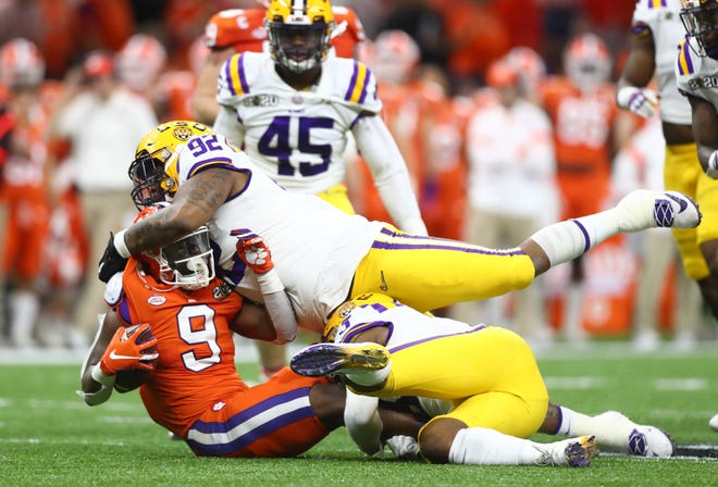 LSU defensive end Neil Farrell Jr. (92) tackles Clemson running back Travis Etienne (9) during the College Football Playoff national championship game