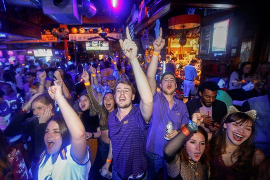 Justin Rogstad, center, cheers on LSU against Clemson in the NCAA College Football Playoff championship game, while watching on screens at Fred's Bar & Grill, in Baton Rouge, La., Monday, Jan. 13, 2020. (AP Photo/Brett Duke)