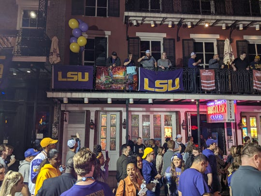 LSU fans toss beads on Bourbon Street after the Tigers' 42-25 national championship victory of Clemson.