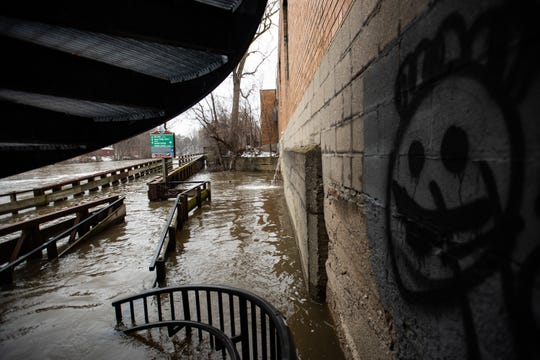 Flooding seen along the Riverwalk Trail in Lansing, Tuesday, Jan. 14, 2020, in Old Town, just north of the Grand River Avenue bridge on Cesar Chavez Avenue.