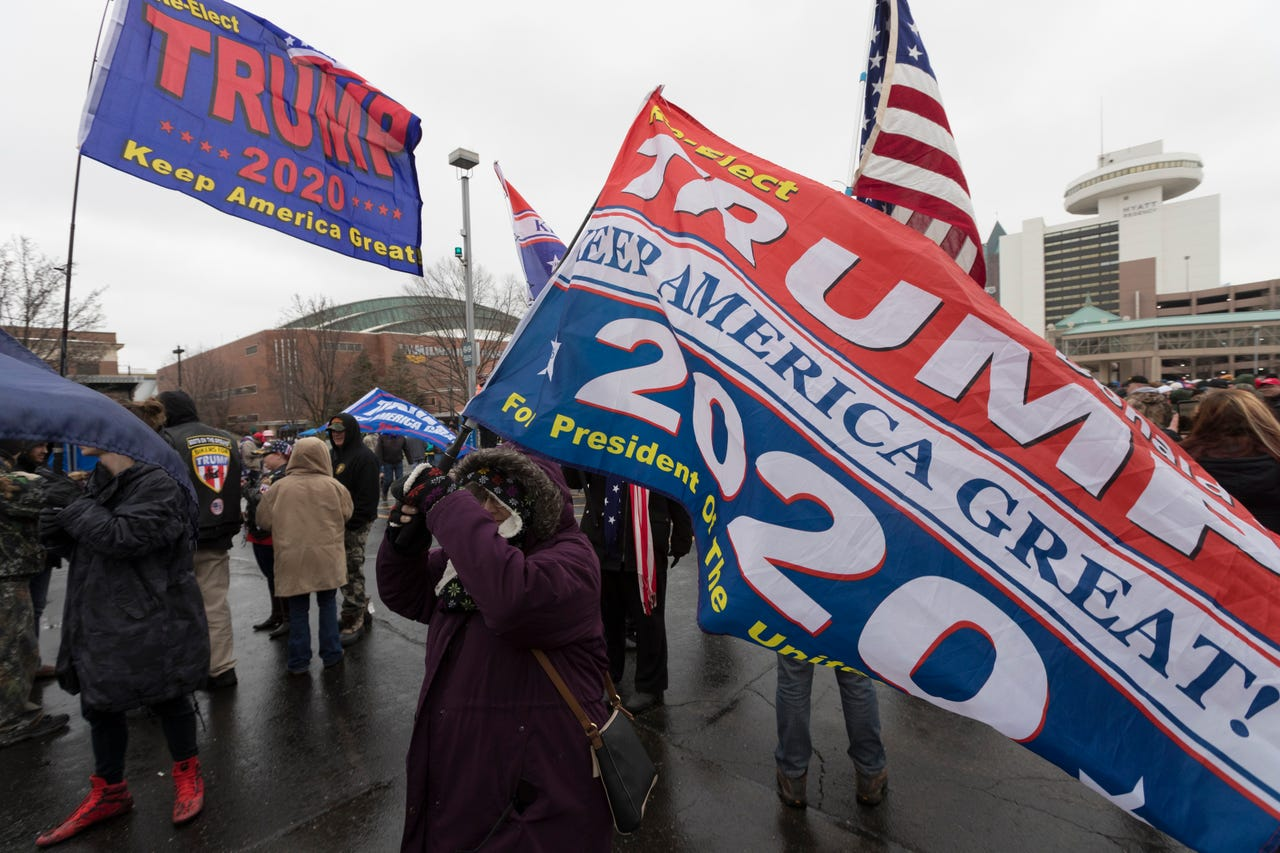 People with Trump flags walk among several thousand people standing in line across the street from the UW-Milwaukee Panther Arena to see President  DonaldTrump Tuesday.