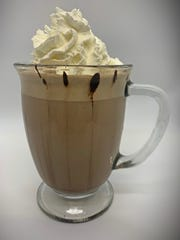 The cup of thevanilla mint hot cocoa fromBlüm Coffee Garden is drizzled withGuittard chocolate syrup. The drink has Monin vanilla and frosted mint syrups, and is topped with whipped cream.