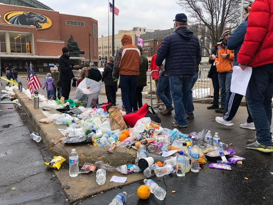 A large pile of trash grows in the parking lot across the street from the arena as attendees discard food and other prohibited items.