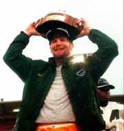 Green Bay Packers quarterback Brett Favre holds high over his head the NFC Championship trophy after the Packers' 23-10 win over the San Francisco 49ers at San Francisco's 3Com Park, Sunday, Jan. 11, 1998.
