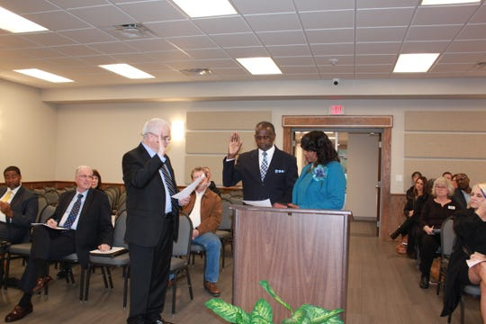 Ouachita Parish School Board attorney Elmer Noah (left) leads interim school board member Harold McCoy in his oath of office at a meeting on Tuesday.
