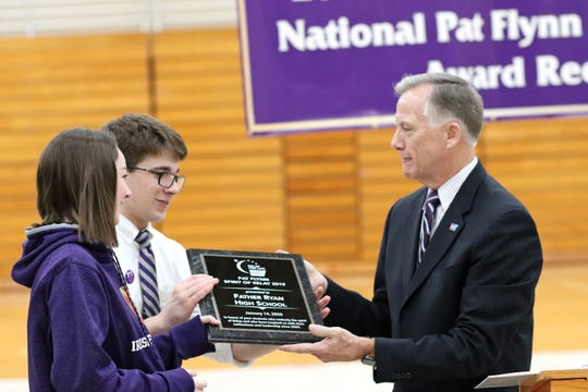 Gary Reedy, the CEO of the American Cancer Society, presents the Spirit of Relay award to Father Ryan High School students Madison Ahern, left, and Danny Farone, who co-chaired the school's 2019 Relay for Life event, which generated $214,000 to fight cancer.