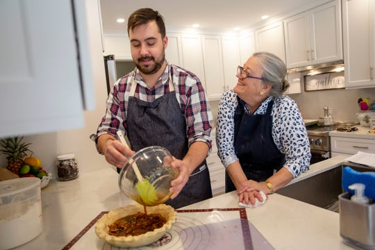 """Sheila Varnum, right, teaches Naples Daily News reporter Andrew Atkins, left, how to bake a bittersweet chocolate pecan pie at her home in Naples on Jan. 13, 2020. """"Baking is the work of the soul and the heart, I think,"""" said Varnum, who regularly teaches baking classes for her friends."""