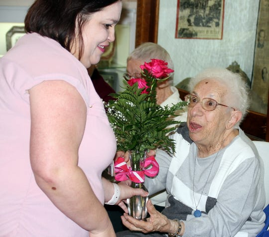 Mimbres Memorial Hospital and Nursing Home Secretary Mary Hopper, right, received a vase of roses during Sunday's get-together at the Deming-Luna-Mimbres Museum honoring the auxiliary members for the past 61 years of volunteerism.