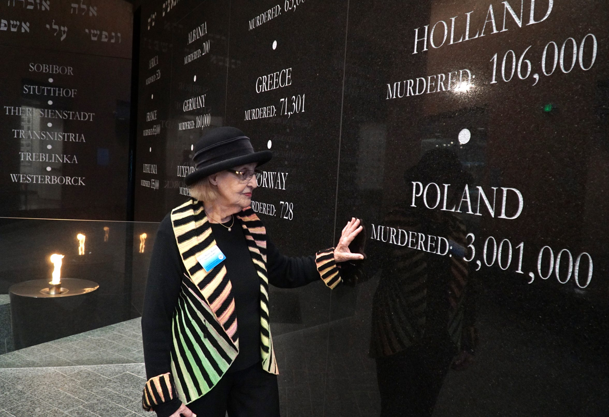 Near an eternal flame, Paula Marks-Bolton stops by an wall engraving at the Holocaust Memorial Center in Farmington Hills on Jan.14, 2020. The engraving notes how many Polish Jews perished in the Holocaust. Marks-Bolton grew up in Poland and was sent to a series of concentration camps beginning soon after she was 13 years old.