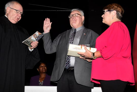 Judge James P. Doherty Jr. administers the oath of office to St. Landry Parish President Bill Fontenot while his wife, Patsy, witnesses the event Monday at the Delta Grand Theater.