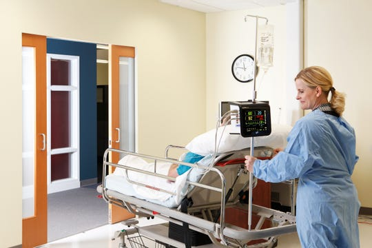 Patient and nurse modeling the patient monitoring system.