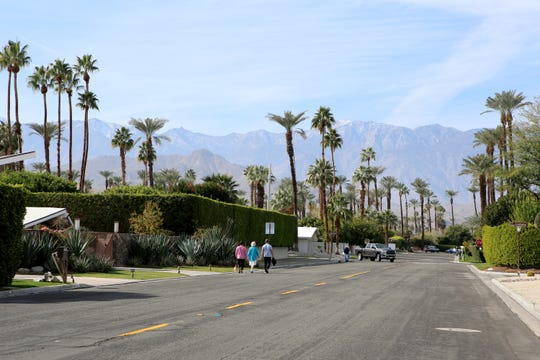 People walk along Tamarisk Lane Tuesday in Rancho Mirage near where several home burglarlies have been reported.