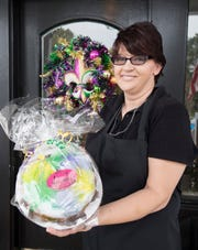 Tegan Puckett holds a king cake for sale at Adonna's Bakery & Cafe in Pensacola on Tuesday, Jan. 14, 2020.