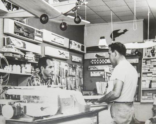 Terry Bobe, left, helps a customer at Bobe's Hobby House in Pensacola in this vintage photo. The iconic store is closing and auctioning off its inventory starting Saturday.