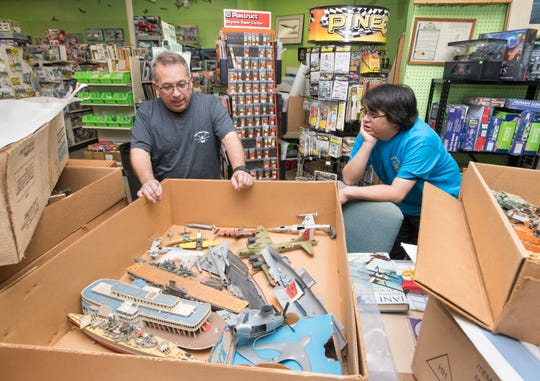 Owner Mike Bobe, left, and clerk Khang Hoang look over a box of vintage models Jan. 13 at Bobe's Hobby House in Pensacola.