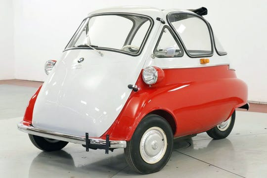 This two-tone red and white 1956 BMW Isetta 300 has a bubble top with a sunroof, chrome and a cream interior.