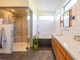 Finishes in the master bathroom complement the industrial look throughout the home.