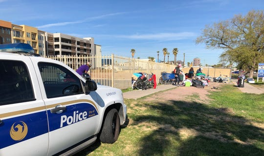 Phoenix officers monitor a group of homeless people who were camped out along Third Street near Roosevelt Street in Phoenix on Jan. 14, 2020.