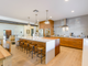 The home's open kitchen includes a mix of wood, a custom butcher block-waterfall edge island and two sinks.