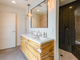 The home's guest bathroom includes a custom vanity, touched off with industrial lighting.