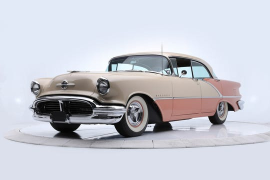 This tan and coral 1956 Oldsmobile Super 88 features a dual exhaust and period-correct upholstery.