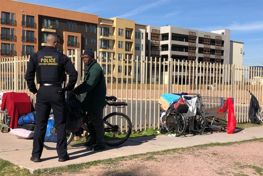 A Phoenix officer talks to homeless people who were camped out along Third Street near Roosevelt Street on Jan. 14, 2020.