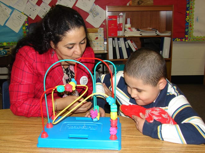 Fotografía de una mujer mientras juega con un niño autista en un centro de educación de México.
