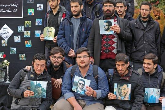 Estudiantes iraníes protestan sosteniendo fotos de las víctimas dle avión ucraniano derribado en Irán.