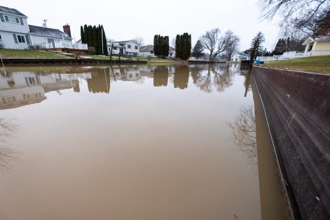 Water rises almost to the top of a seawall in a canal along the Black River in 2020. To prepare for potential flooding, the city of Port Huron is preparing to distribute sandbags to residents in flood-prone areas.