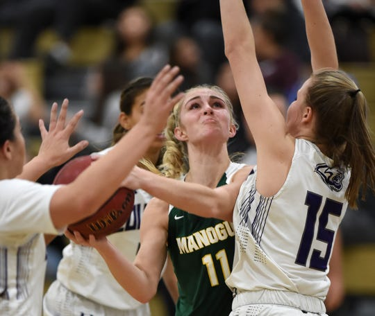 Bishop Manogue's Kenna Holt is surrounded by Spanish Spring Cougars as she looks to shoot  on Jan. 9, 2020.