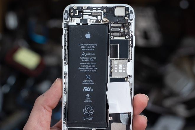 "An iPhone with a lithium ion battery has been disassembled at the Sunnking facility in Brockport, New York. A warning on the battery reads, ""Potential for fire or burning. Do not disassemble, puncture, crush, heat, or burn."" Lithium ion batteries must be carefully removed from discarded electronics because if damaged, an electrical short can start a fire."