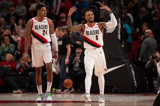 Portland Trail Blazers guard Damian Lillard (0) encourages fans to cheer after making a shot during the second half against the Charlotte Hornets at Moda Center.