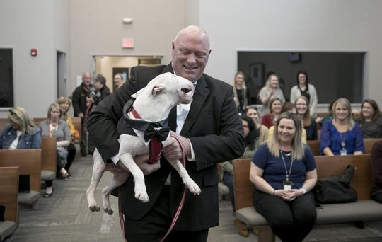 Round Rock police officer John Schultz carries Champ, a 3-year-old bull terrier, into the courtroom of Williamson County Justice of the Peace Evelyn McLean at the Williamson County Georgetown Annex where he officially adopted the dog on Monday January 13, 2020. Champ was severely injured on August 10, 2019, when his former owner dragged him behind a truck.
