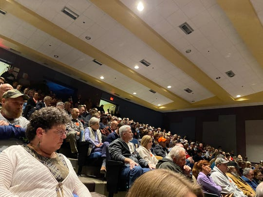 "A view of the full auditorium. Many gun-rights advocates wore orange ""Guns save lives"" stickers."