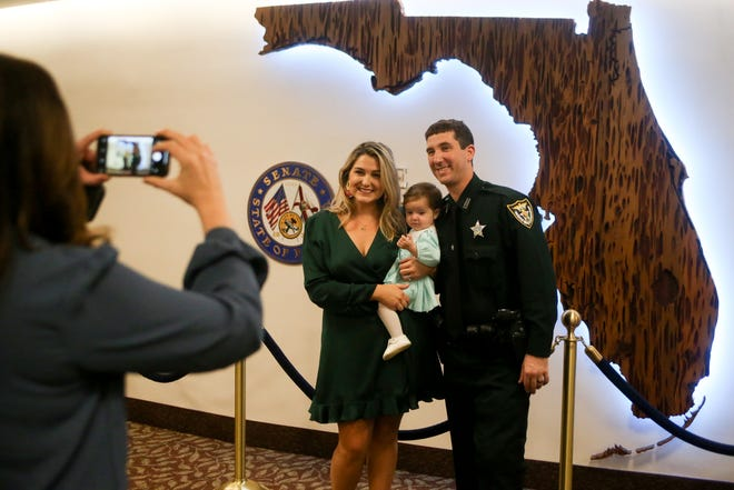 Escambia County Sheriff's Deputy Matthew Tinch, his wife and daughter pose for photo in front of the Senate gallery after Tinch was honored by the Senate for his role in responding to the December NAS Pensacola shooting Tuesday, Jan. 14, 2020.