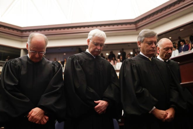 Members of the Florida Supreme Court bow their heads in prayer before the governor's State of the State speech on the first day of the 2020 legislative session Tuesday, Jan. 14, 2020.