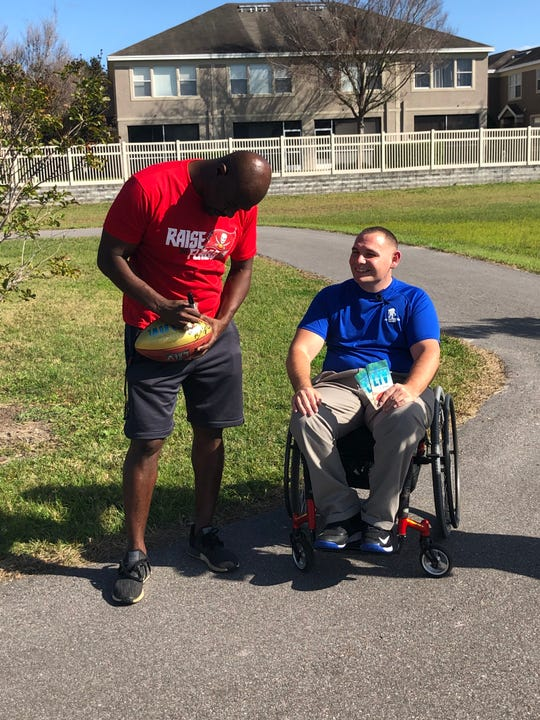 Former Tampa Bay Buccaneers Super Bowl MVP Dexter Jackson of Quincy autographs a football for injured veteran and wounded warrior Mike Delancey Monday afternoon in Pinellas Park, Florida.