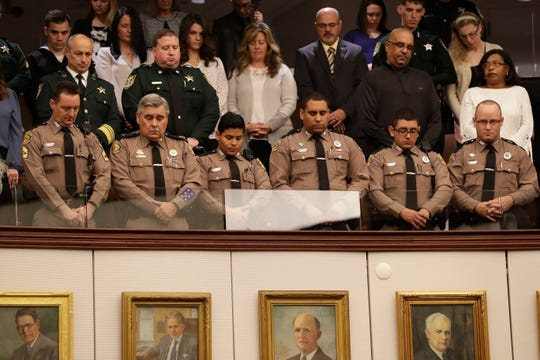 Members of the Florida Highway Patrol stand and bow their heads during a moment of silence held in remembrance of the victims of the December shooting at NAS Pensacola in the Senate chamber Tuesday, Jan. 14, 2020.