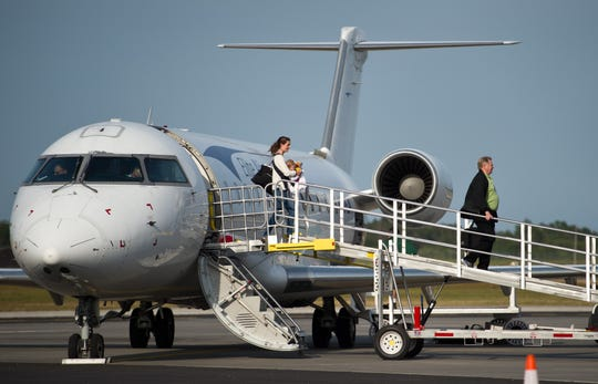 Meghan Carson (center), of New York City, carries her 7-month-old daughter, Ellie, as she disembarks the Elite Airways flight that arrived at Vero Beach Regional Airport non-stop from Newark Liberty International Airport on Thursday, March 17, 2016, in Vero Beach. The pair travelled to Vero Beach to visit Ellie's grandmother, Deidre Renehan.