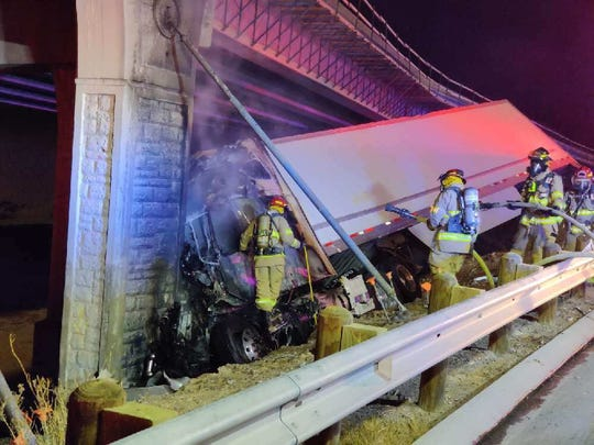 The driver of the semitruck lost control and struck a barrier on the highway, causing the truck to go up in flames, officials said.