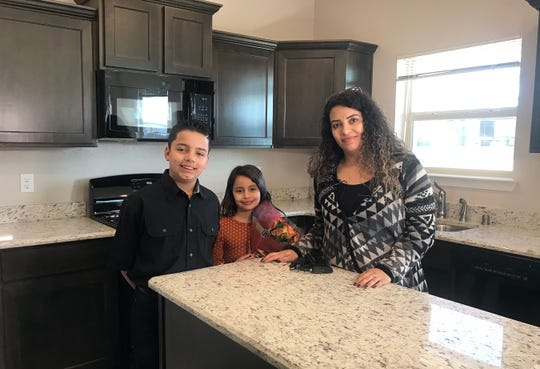 Lorena Mendez, the widow of Marine Lance Cpl. Norberto Mendez-Hernandez, stands with their children Anthony and Audrey in their new home.