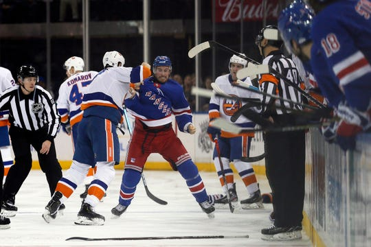 Jan 13, 2020; New York, New York, USA; New York Rangers defenseman Brendan Smith (42) fights New York Islanders left wing Matt Martin (17) during the first period at Madison Square Garden. Mandatory Credit:  Adam Hunger-USA TODAY Sports