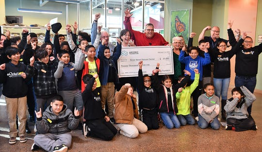 Liz Martin of River Bend Nature Center and Howard McDaris of Arconic, center, celebrate Arconic Foundation's grant of $20,000 to RBNC with students from Scotland Park Elementary Tuesday morning.