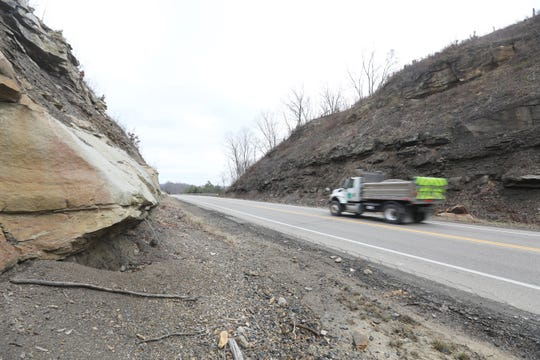 An Ohio Department of Transportation truck passes through a rock cut on US 22 near White Cottage. The road will be closed for 45 days to widen the cuts starting Monday.