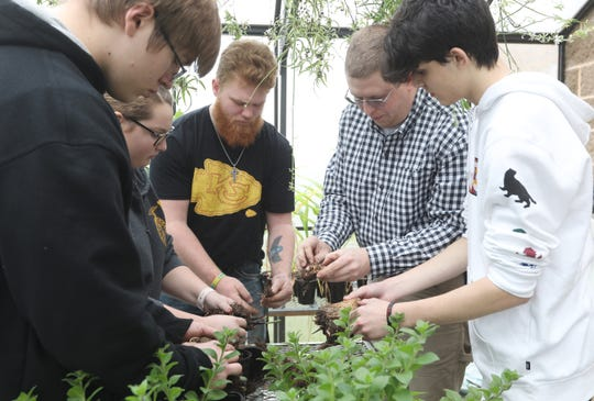 Jeremy Ryan, second from right, works with his class at West Muskingum High Schoolin the school's greenhouse. Ryan was recently announced as one of the 10 finalists in Ohio for the Ag Educator of the Year honorthrough Nationwide's Golden Owl Award program.