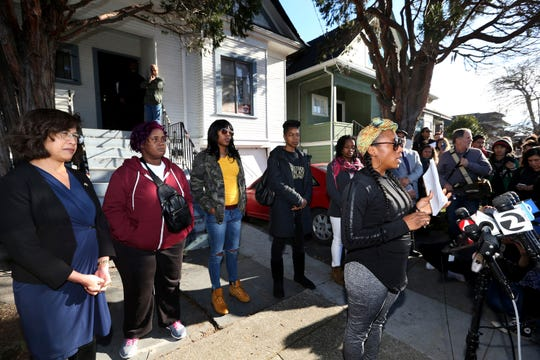 Dominique Walker, right, speaks for herself and on behalf of fellow Moms 4 Housing members Sharena Thomas, second from left, Misty Cross, and Tolani King, as councilwoman Nikki Fortunato Bas, left, looks on during a press conference outside the house they have occupied in Oakland, Calif., Friday, Jan. 10, 2020. The women were removed from the house they had illegally been occupying since November as a way of spotlighting the Bay Area and California's ongoing housing crisis.