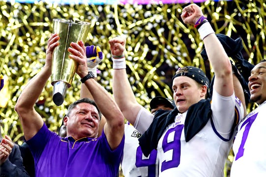 LSU Tigers head coach Ed Orgeron and quarterback Joe Burrow celebrate with the national championship trophy.