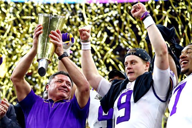 LSU Tigers head coach Ed Orgeron and quarterback Joe Burrow celebrate with the national championship trophy.