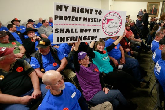 Gun rights protesters hold signs before the start of a meeting of the Senate Judiciary committee at the Capitol in Richmond, Va., Monday, Jan. 13, 2020.